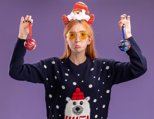 Trauriges junges schönes mädchen mit weihnachtspullover und weihnachtshaarreifen mit brille, die weihnachtskugeln einzeln auf lila wand hebt