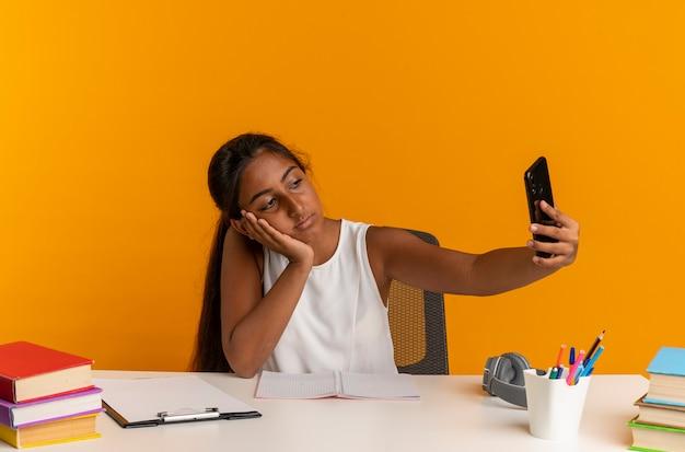 Trauriges junges schulmädchen, das am schreibtisch mit schulwerkzeugen sitzt, die kopf auf hand setzen und selfie lokalisiert auf orange wand nehmen