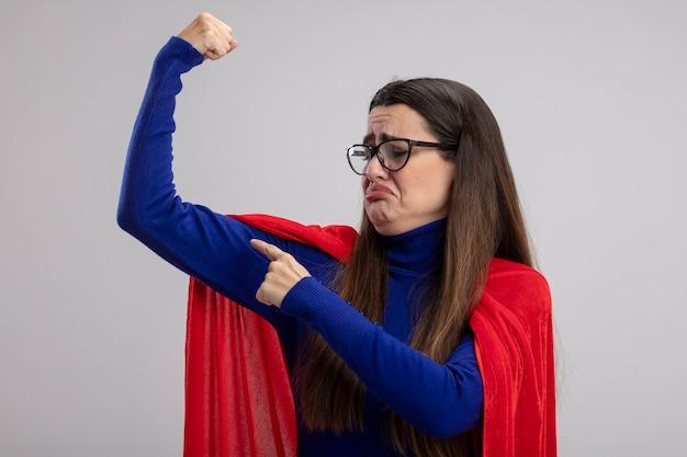Trauriges junges superheldenmädchen, das brillen trägt, die starke geste lokalisiert auf weißem hintergrund zeigen