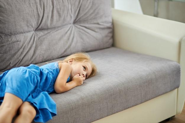 Trauriges kaukasisches kleines mädchen, das allein auf sofa liegt und verärgert wegschaut