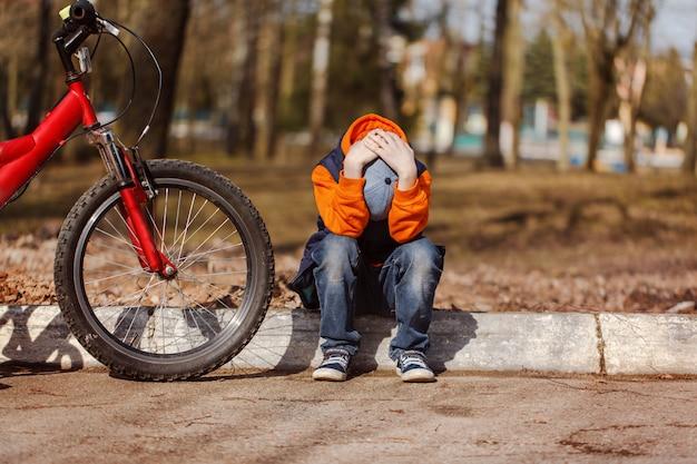 Trauriges kind, das nahe einem defekten fahrrad sitzt