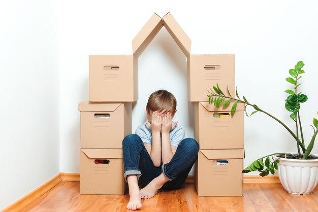 Trauriges kind, das sich im haus versteckt aus kisten versteckt. hypothek, menschen, wohnen, umzug und immobilien.