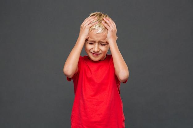 Trauriges kind des kleinen jungen mit kopfschmerzen