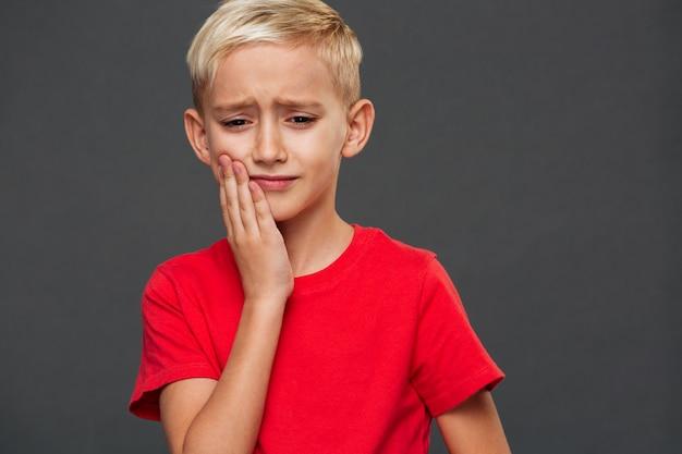 Trauriges kind des kleinen jungen mit zahnschmerzen