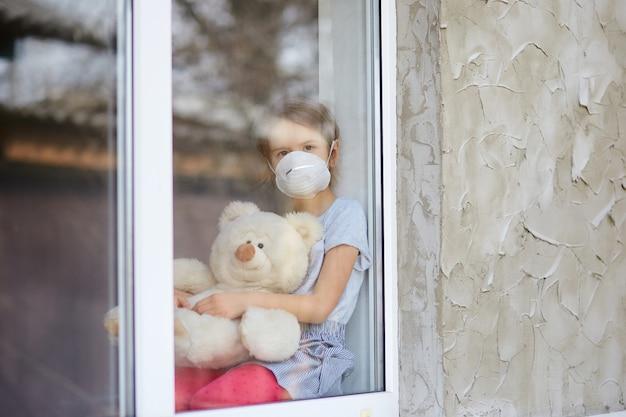 Trauriges kind, kleines mädchen in der maske mit teddybär, der vom fenster schaut, coronavirus-quarantäne, hauptschule. blick von der straße. bleib zuhause. konzept des coronavirus