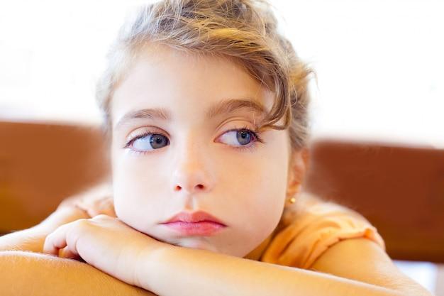 Trauriges kindermädchen der blauen augen kreuzte arme