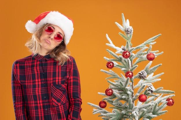 Trauriges, kippendes junges schönes mädchen, das in der nähe des weihnachtsbaums steht und weihnachtsmütze mit brille auf orangefarbenem hintergrund trägt