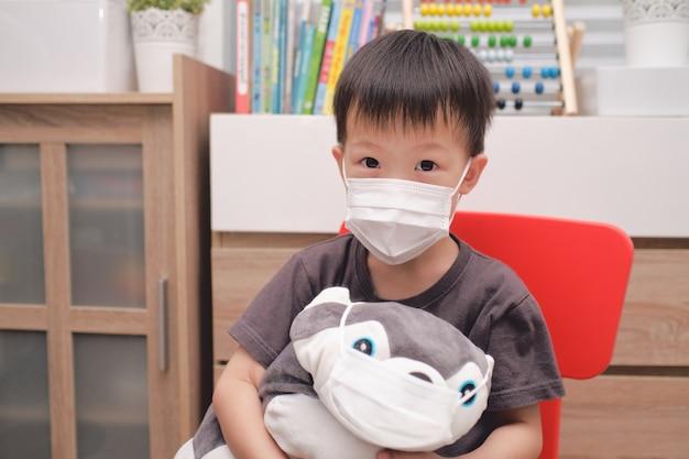 Trauriges kleines asiatisches jungenkind und sein hundplüschtier beide in medizinischen schutzmasken, gesichtsmasken