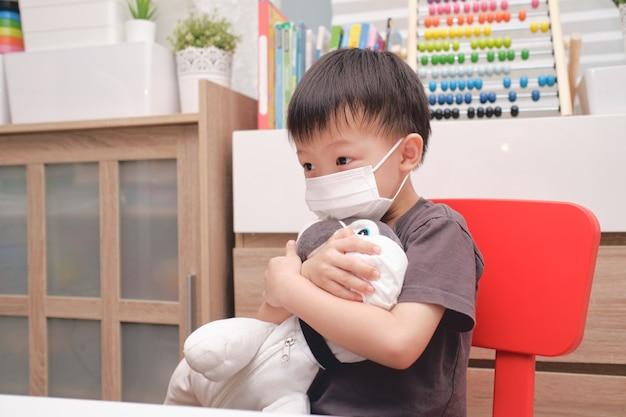 Trauriges kleines asiatisches kindergartenkind, das sein plüschtier des hundes sowohl in medizinischen schutzmasken als auch in gesichtsmasken umarmt