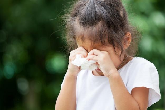 Trauriges kleines asiatisches mädchen, das gewebe auf ihrer hand schreit und hält
