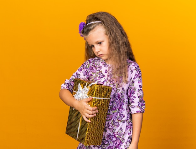 Trauriges kleines blondes mädchen, das geschenkbox isoliert auf oranger wand mit kopienraum hält