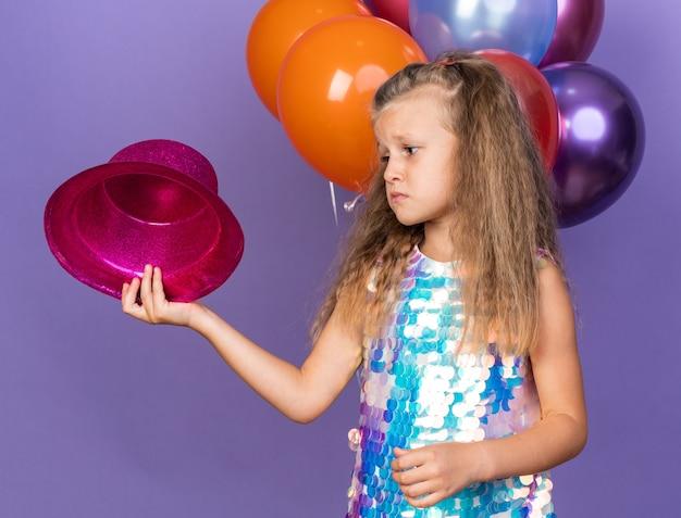 Trauriges kleines blondes mädchen, das violetten partyhut hält und anschaut, der mit heliumballons steht, isoliert auf lila wand mit kopierraum