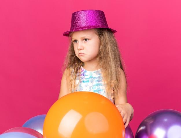 Trauriges kleines blondes mädchen mit lila partyhut, das mit heliumballons steht und seitlich isoliert auf rosa wand mit kopienraum schaut