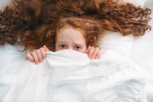 Trauriges kleines mädchen ängstlich, schlafende und ziehende steppdecke auf kopf.