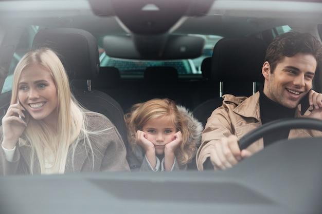 Trauriges kleines mädchen, das im auto sitzt, während ihre eltern sprechen