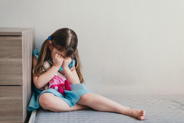 Trauriges kleines mädchen, das in ihrem schlafzimmer weint und ihr gesicht mit den händen bedeckt