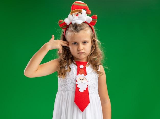 Trauriges kleines mädchen, das weihnachtshaarreifen mit krawatte trägt, das ohr isoliert auf grüner wand kratzt