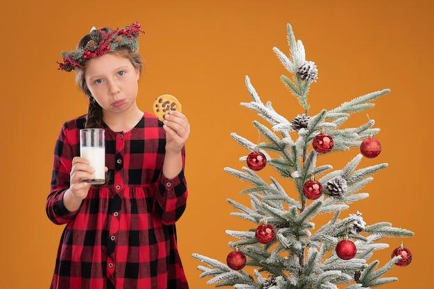 Trauriges kleines mädchen, das weihnachtskranz im karierten hemd trägt, das glas milch und keks hält und mit traurigem ausdruck auf gesicht schaut