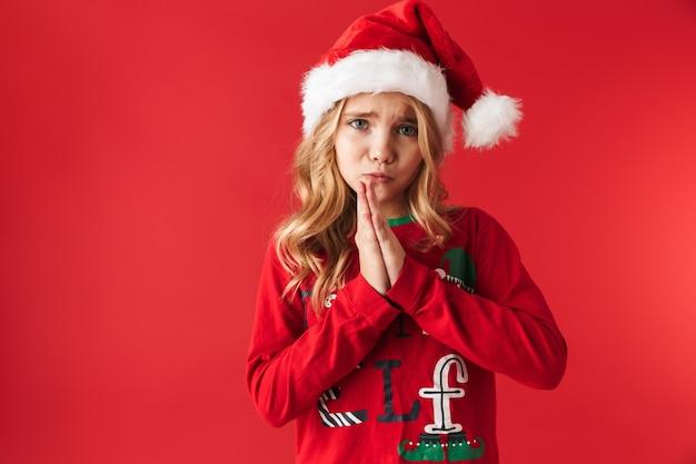 Trauriges kleines mädchen, das weihnachtsmütze trägt, der isoliert steht und um ein geschenk bettelt