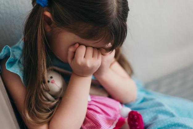 Trauriges kleines mädchen, das weint und ihr gesicht mit handnahaufnahme bedeckt