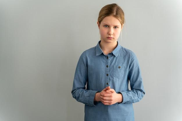 Trauriges kleines mädchen in einem blauen hemd auf einer weißen wand