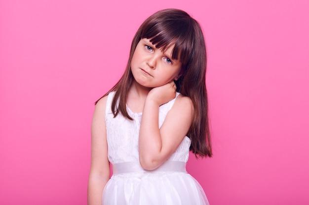 Trauriges kleines mädchen in einem eleganten weißen kleid, das nach vorne schaut, gelangweilt ausdrückt, verärgert oder beleidigt ist, hand auf ihrem hals hält, isoliert über rosa wand