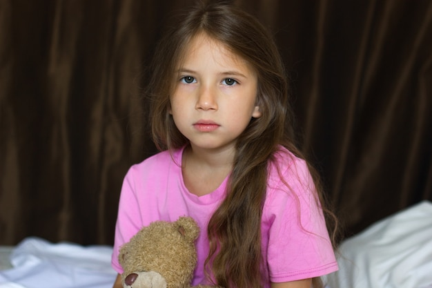 Trauriges kleines mädchen mit langen blonden haaren im bett mit einem teddybären während des tages schaut in die kamera