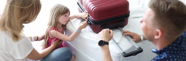 Trauriges kleines mädchen schaut auf den koffer, der neben ihren eltern sitzt