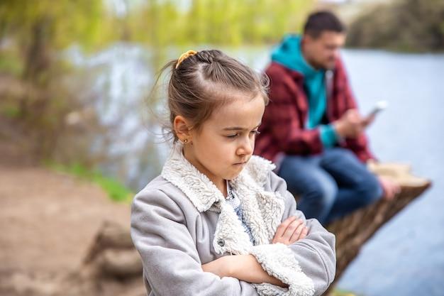 Trauriges kleines mädchen, weil papa beim spaziergang im wald sein telefon überprüft und sie nicht beachtet.