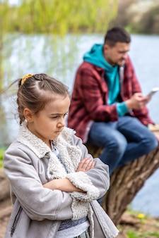 Trauriges kleines mädchen, weil papa sein telefon überprüft, während er im wald spazieren geht und ihr keine aufmerksamkeit schenkt.
