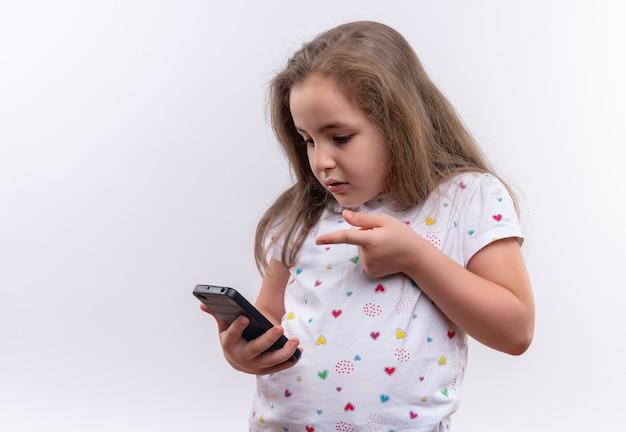 Trauriges kleines schulmädchen, das weiße t-shirt-punkte am telefon auf lokalisiertem weißem hintergrund trägt