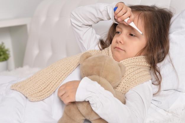 Trauriges krankes kleines mädchen, das mit teddybärspielzeug im bett liegt