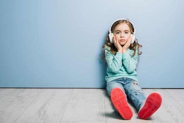 Trauriges mädchen, das auf boden gegen hörende musik der blauen wand auf kopfhörer sitzt