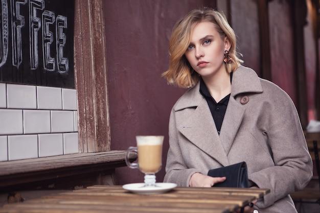 Trauriges mädchen in einem straßencafé wird für eine tasse köstlichen cappuccino bezahlen