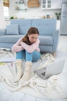 Trauriges mädchen in gestrickten socken, die auf dem boden sitzen und einen laptop betrachten.