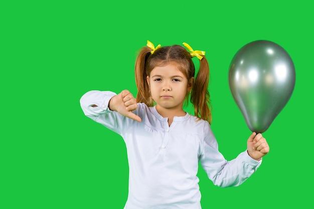 Trauriges mädchen mit blonden pferdeschwänzen und ultimativen grauen ballon zeigt daumen nach unten Premium Fotos