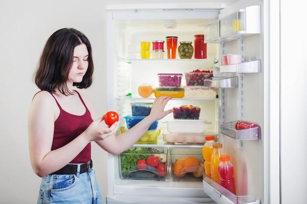 Trauriges mädchen mit tomate nahe offenem kühlschrank