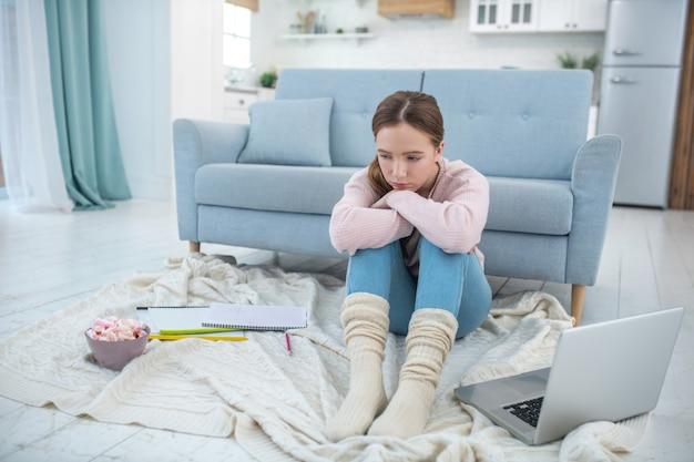 Trauriges mädchen sitzt auf einem plaid auf dem boden mit dem rücken zum sofa neben einem laptop.