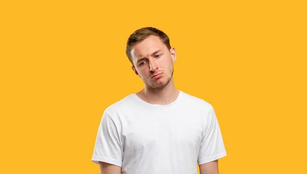 Trauriges mannporträt. misserfolg enttäuschung. verärgerter kerl im weißen t-shirt auf orangem hintergrund.