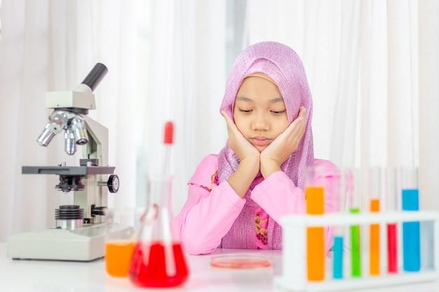 Trauriges muslimisches mädchen, das wissenschaft studiert