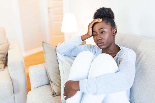 Trauriges, nachdenklich besorgtes afroamerikanisches mädchen sitzt auf dem sofa und schaut weg