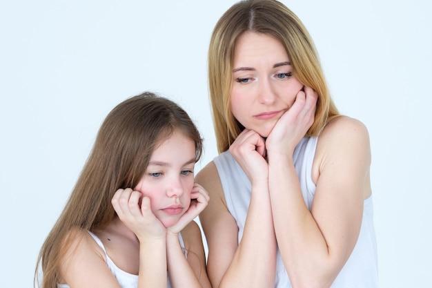 Trauriges nachdenkliches einsames paar von mutter und tochter. stürze des familienlebens und unangenehme situationen