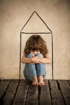 Trauriges obdachloses kind, das im dunklen raum auf dem boden sitzt