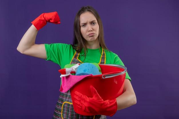 Trauriges putzendes junges mädchen, das uniform in handschuhen hält, die reinigungswerkzeuge halten, die starke geste auf lila hintergrund tun