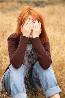 Trauriges rothaarigemädchen, das auf gelbem gras an der landschaft sitzt