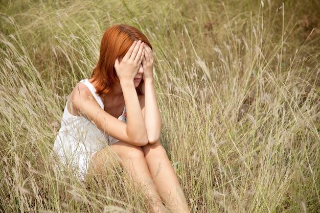Trauriges rothaariges mädchen am gras.