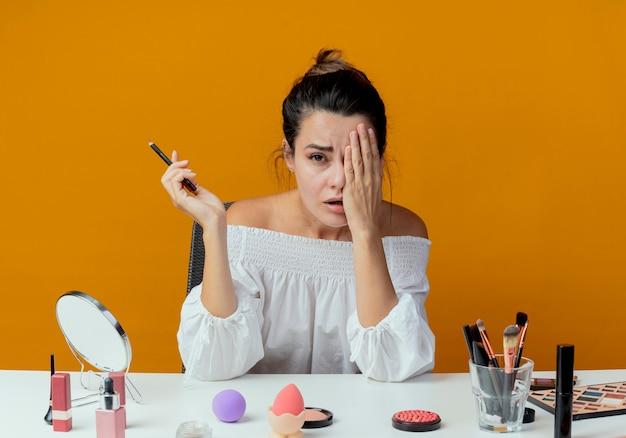 Trauriges schönes mädchen sitzt am tisch mit make-up-werkzeugen schließt auge mit hand, die eyeliner hält, der lokal auf orange wand schaut