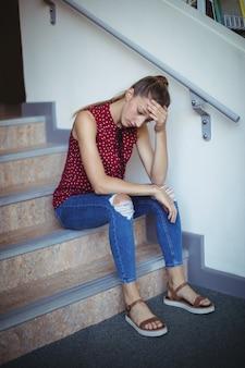 Trauriges schulmädchen, das allein auf treppe sitzt