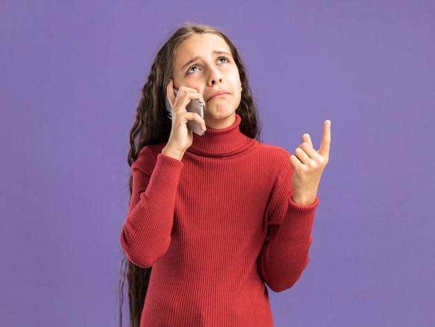 Trauriges teenager-mädchen, das am telefon spricht und nach oben zeigt, isoliert auf lila wand mit kopierraum?
