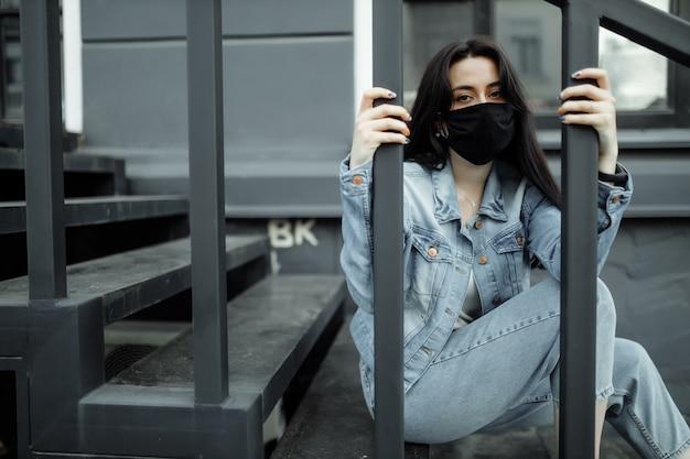 Trauriges teenager-mädchen in der medizinischen maske hinter gittern. schulen werden aufgrund von krankheit und epidemien unter quarantäne gestellt. coronavirus pandemie. covid 19